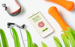 Healthy Goals concept. Fitness healthy goals with mockup mobile phone on white table with dumbbells,smart watch, earphone. Mock up