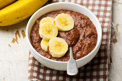 Healthy gooey chocolate banana oatmeal for breakfast. Selective focus Stock Images