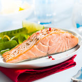 Healthy gourmet pink salmon steak. Rich in omega-3 served with fresh green mangetout peas and lemon, close up showing the texture of the fish stock image