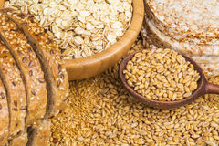 Healthy grains, cereals and whole wheat bread. Variety of grains: rolled oats, golden linseeds (flax seeds), whole wheat grains and buckwheat cakes. Soft focus Royalty Free Stock Image