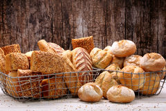 Healthy grainy bread in metal basket on wooden background Stock Photos