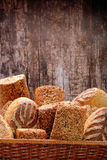 Healthy grainy bread in wicker basket on wooden background Stock Photos