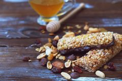 Healthy granola bars with dried fruits, nuts and honey on wooden background. Healthy granola bars with fruits, nuts and honey on wooden background.Cereal bars Royalty Free Stock Images