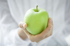 Healthy green apple. Closeup shot of a woman holding healthy green apple. Girl with a green apple in hands. Shallow depth of field with focus on the green apple Stock Photo