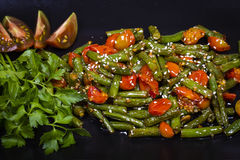 Healthy green beans, red cherry tomato with sesame seeds. Cooked green beans, red cherry tomato with sesame seeds in black plate, close up Stock Photography