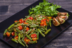 Healthy green beans, red cherry tomato with sesame seeds. Cooked green beans, red cherry tomato with sesame seeds in black plate, close up Royalty Free Stock Photography