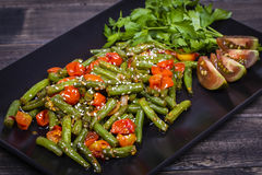 Healthy green beans, red cherry tomato with sesame seeds. Cooked green beans, red cherry tomato with sesame seeds in black plate, close up Royalty Free Stock Photo