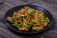 Healthy green beans, red cherry tomato with sesame seeds. Cooked green beans, red cherry tomato with sesame seeds in black plate, close up Stock Image