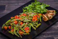 Healthy green beans, red cherry tomato with sesame seeds. Cooked green beans, red cherry tomato with sesame seeds in black plate, close up Royalty Free Stock Image