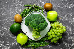 Healthy green food with fresh vegetables on dark table background top view. Healthy green food with fresh vegetables on dark kitchen table background top view Royalty Free Stock Photos