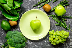 Healthy green food with fresh vegetables on dark table background top view. Healthy green food with fresh vegetables on dark kitchen table background top view Royalty Free Stock Photo