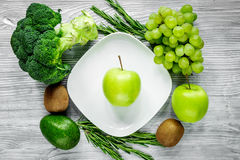 Healthy green food with fresh vegetables on gray wooden table background top view. Healthy green food with fresh vegetables on gray wooden kitchen table Stock Images