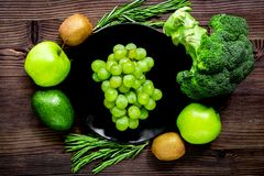 Healthy green food with fresh vegetables on wooden table backgro. Healthy green food with fresh vegetables on wooden kitchen table background top view Royalty Free Stock Photo