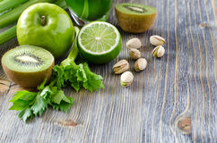 Healthy green food ingredients for making smoothie. Green apple, kiwi, celery, pistachio nuts copy space background Royalty Free Stock Photography