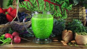 Healthy Green Juice. Pouring Healthy Green Juice on a table filled with vegetables and fruits stock video footage