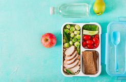 Healthy green meal prep containers with chicken fillet, rice, brussels sprouts. And vegetables overhead shot with copy space. Dinner in lunch box. Top view stock photo