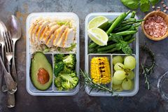 Healthy green meal prep containers with rice and vegetables. Healthy green meal prep containers with chicken, rice, avocado and vegetables overhead shot stock photo