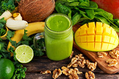 Healthy Green Reach Vitamins Smoothie with baby leaf spinach, kale, mango, banana, lime, walnut and coconut water. Royalty Free Stock Image