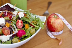 Healthy green salad and an apple with measuring tape. Fresh and healthy green salad for healthy life Royalty Free Stock Image