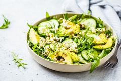 Healthy green salad with avocado, cucumber and arugula in white dish. Plant based diet concept stock images