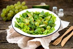 Healthy green salad from avocado, cucumber, grapes, parsley and lettuce with olive oil dressing, balsamic vinegar and grain mustar. D. tasty food royalty free stock images