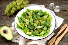 Healthy green salad from avocado, cucumber, grapes, parsley and lettuce with olive oil dressing, balsamic vinegar and grain mustar. D.  tasty food Royalty Free Stock Image