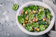 Healthy green salad bowl with spinach, quinoa, chickpeas and red onions. On gray background Stock Photo
