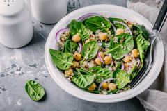 Healthy green salad bowl with spinach, quinoa, chickpeas and red onions. On gray background Stock Image