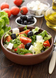 Healthy green salad with feta, olives and tomatoes in the bowl on the wooden table. Royalty Free Stock Image