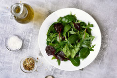 Healthy green salad. With leaves of spinach, arugul on light background. Top view Stock Photo