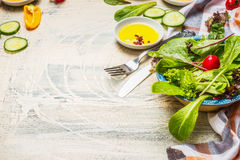 Healthy green salad preparation with dressing and cutlery on white rustic background. Diet eating, Vegetarian or vegan Royalty Free Stock Images