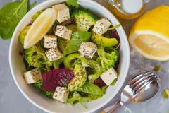 Healthy green salad with tofu, broccoli, avocado, peas and chia. Healthy green salad with broccoli, avocado, peas and chia seeds. Vegan trend food concept Royalty Free Stock Images