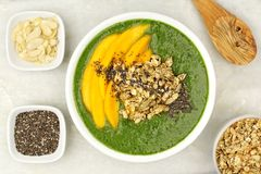Healthy green smoothie bowl overhead view on granite. Green smoothie bowl with mangoes, granola, almonds and chia seeds, overhead view on white granite Royalty Free Stock Images