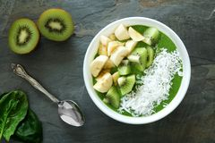 Healthy green smoothie bowl on slate. Green smoothie bowl with spinach, bananas, kiwi and coconut on a slate background Royalty Free Stock Photos