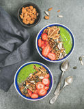Healthy green smoothie breakfast bowls with granola, fruit, seeds, almonds Stock Images
