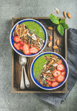 Healthy green smoothie breakfast bowls with granola, fruit, seeds Stock Images