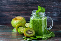 Healthy green smoothie on a dark wooden background. Vegetarian food concept, detox, fitness. Stock Images