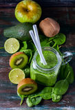 Healthy green smoothie on a dark wooden background. Vegetarian food concept, detox, fitness. Royalty Free Stock Photography