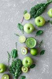 Healthy green smoothie with fresh green fruits, kale and spinach on gray background, top view.  Stock Photos