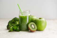 Healthy green smoothie and ingredients. Spinach smoothie in glass jar with apple, spinach and kiwi stock photo