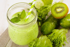 Healthy green smoothie in jar with cucumber, kiwi, salad and spices Stock Image