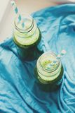 Healthy green smoothie made from spinach, apple and cucumber in a jars with blue straw. On white wooden table. Toned royalty free stock image