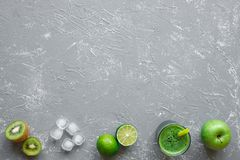 Healthy green smoothie with ripe lime, apple, kiwi and ice cubes on gray background, top view.  royalty free stock photography