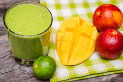 Healthy green  smoothie  from spinach, kiwi, mango,  pineapple and oranges Royalty Free Stock Images