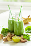 Healthy green spinach smoothie with cilantro lime banana ginger stock image