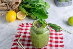 Healthy green spinach smoothie in a jar mug decorated with mint and chia seeds with ingredients on the checkered napkin on the royalty free stock images