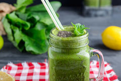 Healthy green spinach smoothie in a jar mug decorated with mint and chia seeds with ingredients on the checkered red napkin on the. Black wooden table Royalty Free Stock Images