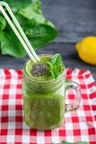 Healthy green spinach smoothie in a jar mug decorated with mint and chia seeds with ingredients on the checkered red napkin on the stock images