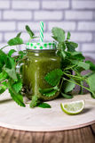 Healthy green spinach smoothie in jar on wooden table, selective focus. Closeup. Royalty Free Stock Photography