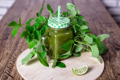 Healthy green spinach smoothie in jar on wooden table, selective focus. Top view. Royalty Free Stock Images